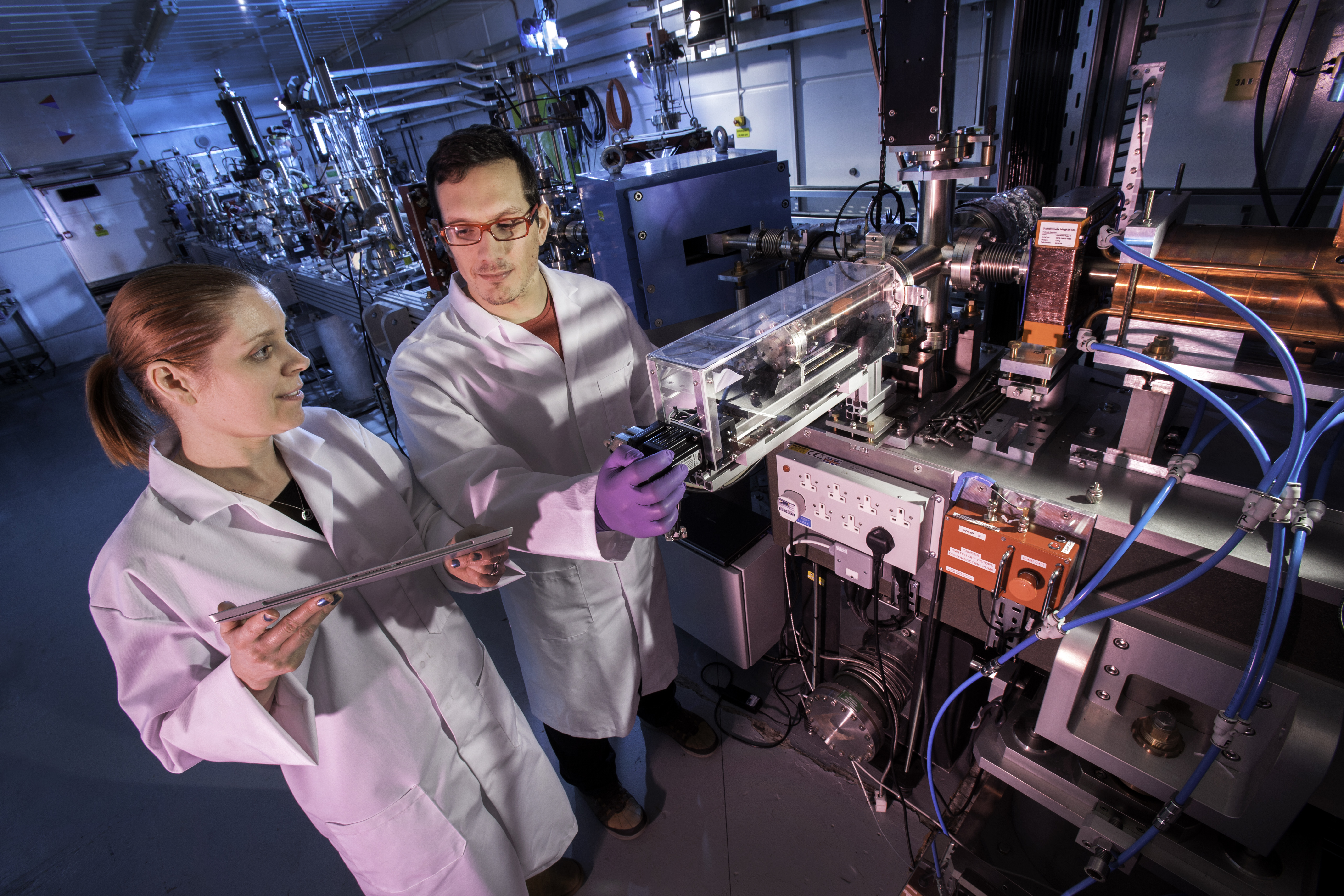 Two people stood alongside a particle accelerator